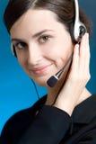 Verticale de jeune femme avec l'écouteur, sur le fond bleu, souriant Photos stock