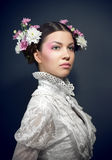 Verticale de jeune femme avec les fleurs fraîches dans le cheveu Photo stock