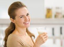 Verticale de jeune femme de sourire avec la glace de lait Photographie stock libre de droits