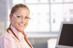 Verticale de jeune femme travaillant dans le sourire de bureau Photographie stock libre de droits