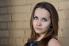 Verticale de jeune fille avec près du mur de briques Image libre de droits
