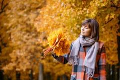 Verticale de jeune fille extérieure Bouquet avec les feuilles jaunes dans des ses mains Femme de brune en parc d'automne avec à l images libres de droits