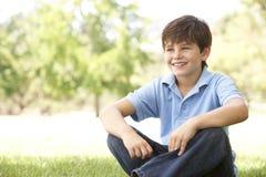 Verticale de jeune garçon se reposant en stationnement photos stock