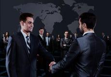 Verticale de jeune gens d'affaires Poignée de main devant des gens d'affaires Photos stock