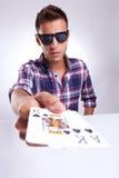 Verticale de jeune homme affichant des cartes de tisonnier Photo stock