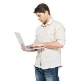 Verticale de jeune homme avec l'ordinateur portable dans les vêtements sport photographie stock