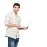 Verticale de jeune homme avec l'ordinateur portable dans les vêtements sport Photo libre de droits
