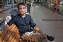Verticale de jeune homme sur le banc dans le mail Image libre de droits