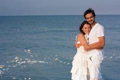 Verticale de jeunes couples dans des vêtements blancs en mer Images libres de droits