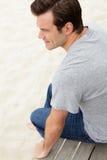 Verticale de l'homme âgé moyen s'asseyant par la plage Image libre de droits