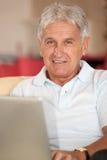 Verticale de l'homme aîné à l'aide de l'ordinateur Images libres de droits