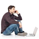 Verticale de l'homme invitant le téléphone avec l'ordinateur portable images libres de droits