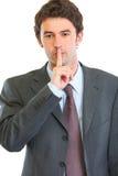 Verticale de l'homme moderne d'affaires affichant le shh Photographie stock libre de droits