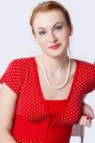 Verticale de la femme de sourire dans un d rouge Images libres de droits