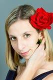 Verticale de la fille avec une rose dans le cheveu Image libre de droits