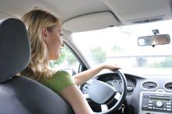 Verticale de la jeune femme de sourire conduisant le véhicule Images libres de droits