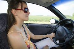Verticale de la jeune femme de sourire conduisant le véhicule Image libre de droits