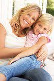 Verticale de la mère et du descendant détendant sur le sofa Image libre de droits