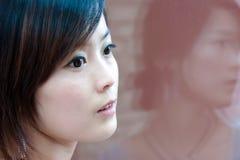 Verticale de la réflexion de fille de ville dans le mur en verre Image libre de droits
