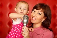 Verticale de mère et de descendant avec le microphone Image stock