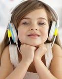 Verticale de petite fille écoutant la musique photographie stock