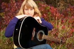 Verticale de plan rapproché d'une jeune fille heureuse avec la guitare Images libres de droits