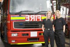 Verticale de rester femelle de deux sapeurs-pompiers images libres de droits