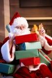Verticale de Santa avec la pile des cadeaux de Noël Photos stock
