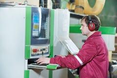 Verticale de travailleur de menuiserie avec la machine de commande numérique par ordinateur image libre de droits