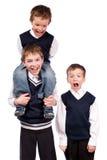 Verticale de trois frères d'amusement dans l'uniforme scolaire Photos libres de droits