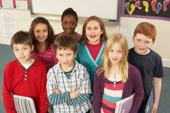 Verticale des écoliers restant dans la salle de classe Photos stock