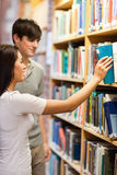 Verticale des étudiants choisissant un livre sur une étagère Images libres de droits