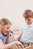 Verticale des enfants de mêmes parents jouant aux échecs Photo stock