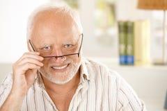 Verticale des glaces s'usantes heureuses d'homme plus âgé