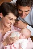 Verticale des parents alimentant la chéri nouveau-née à la maison Image libre de droits