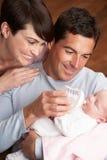 Verticale des parents alimentant la chéri nouveau-née à la maison photo libre de droits