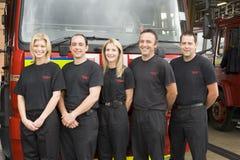 Verticale des sapeurs-pompiers se tenant prêt une pompe à incendie images stock