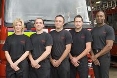 Verticale des sapeurs-pompiers se tenant prêt une pompe à incendie image libre de droits