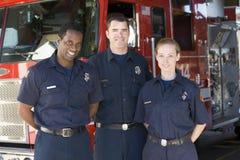 Verticale des sapeurs-pompiers se tenant prêt une pompe à incendie photo stock
