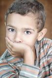 Verticale du garçon mignon de litle couvrant sa bouche Photographie stock libre de droits