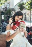 Verticale extérieure Portrait vertical de la belle jeune mariée avec le beau sourire tenant le bouquet de mariage du rouge et du  Photographie stock