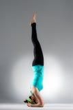 Verticale femminile giovane dello studente di yoga sul pavimento Fotografie Stock