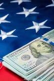 Verticale fotomening van een stapel van geld die op de vlag van de Verenigde Staten van Amerika liggen royalty-vrije stock afbeeldingen