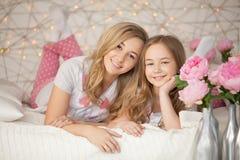 Verticale heureuse de famille Mère et fille étreignant dans le lit dans des pyjamas et regardant l'appareil-photo grenier intérie Photo libre de droits