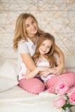 Verticale heureuse de famille Mère et fille étreignant dans le lit et regardant l'appareil-photo dans des pyjamas grenier intérie Photos libres de droits