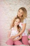 Verticale heureuse de famille Mère et fille étreignant dans le lit et regardant l'appareil-photo dans des pyjamas grenier intérie Photo stock