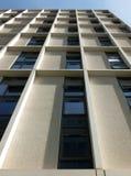Verticale mening van een lang concreet hoekig modern hoog gebouw met geometrische witte details tegen een blauwe hemel stock foto's