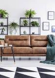 Verticale mening van het moderne binnenland van het koffiehuis met leersofa, kleine lijst en installaties stock afbeelding