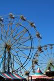 Verticale mening van twee kleurrijke Reuzenraderen in silhouet tegen een heldere blauwe de zomerhemel met tent hieronder paviljoe royalty-vrije stock foto