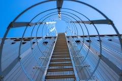 Verticale metaaltrap aan het dak van de hangaar Trap die door een beschermend kader wordt omringd stock fotografie